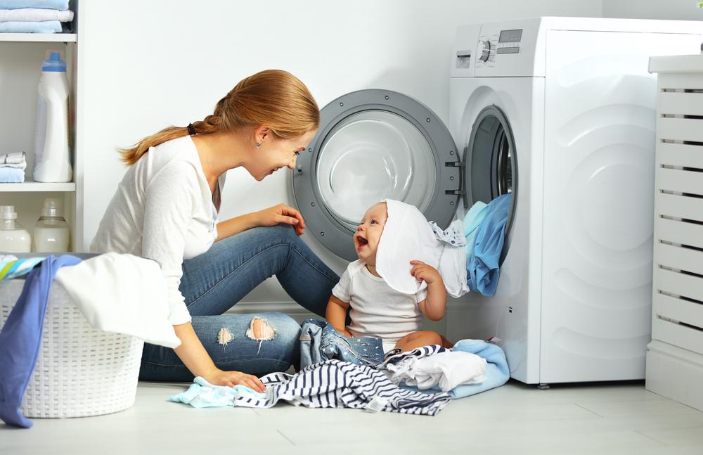 mom and baby near washing machine how to clean a washing machine